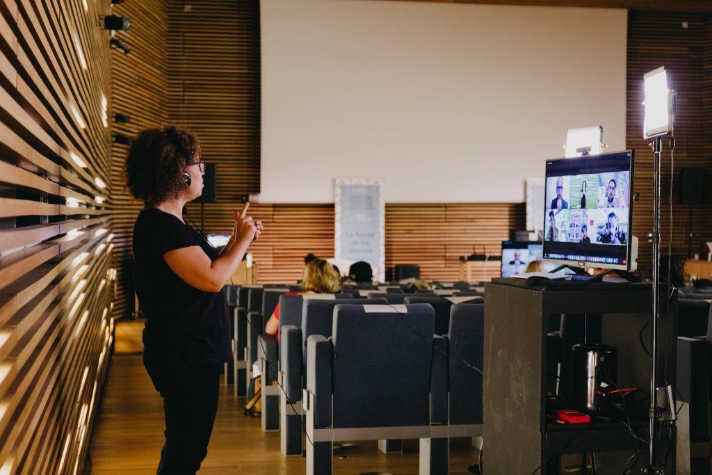 La interprete utiliza la lengua de signos. Mira a una pantalla donde hay varias personas conversando. Ella lleva unos auriculares.