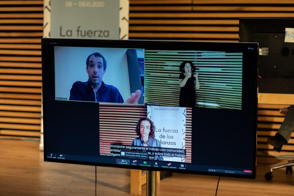 Pantalla donde aparecen 3 personas en una videoconferencia. Una de ellas es la interprete de lengua de signos. Hay subtítulos n la parte inferior.